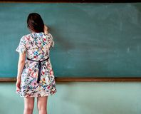 Female teacher at an elementary school in South Korea posing to write something on the blackboard royalty free stock photography