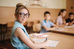 Female teacher in front of children. Pretty teacher in classroom sitting at the desk and asking children. education. Elementary school, learning and people royalty free stock photos