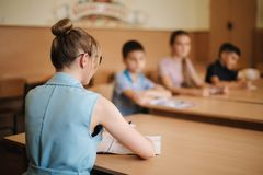 Female teacher in front of children. Pretty teacher in classroom sitting at the desk and asking children. education. Elementary school, learning and people stock photos