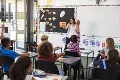 Female teacher gesturing to elementary school class Royalty Free Stock Photo
