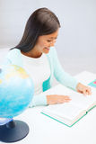 Female teacher with globe and book Stock Photo