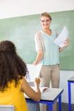 Female teacher handing paper to student Stock Image