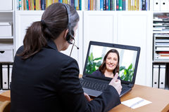 Female teacher headset online course. Female teacher with headset in front of a laptop on her desk giving a private online lesson to an adult student, e-learning Stock Image