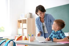 Female teacher helping child with assignment. At school stock photos