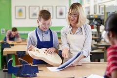 Female Teacher Helping Male High School Student Building Guitar. Female Teacher Helps Male High School Student Building Guitar In Woodwork Lesson Royalty Free Stock Photo