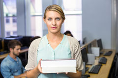 Female teacher holding books in computer class Stock Images