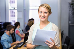 Female teacher holding document in computer class. Portrait of female teacher holding document in computer class Royalty Free Stock Image