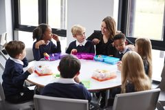 Female teacher kneeling to talk to a group of primary school kids sitting together at a round table eating their packed lunches royalty free stock images