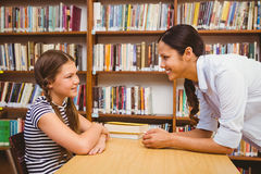 Female teacher and little girl in library Royalty Free Stock Photos