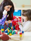 Female teacher and little girl playing Stock Photography