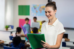 Female teacher looking at files. Happy female teacher looking at files while standing in classroom Royalty Free Stock Photography