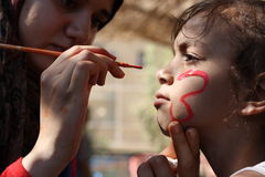 children expressions Female teacher painting little girls face in butterfly shape in playground Stock Photo