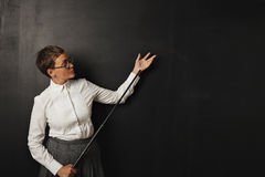 Female teacher with pointer at blackboard. Serious looking young white female teacher in white button up blouse and tweed skirt stands at a black chalkboard royalty free stock images