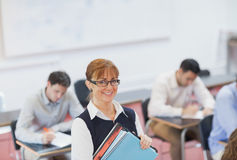 Female teacher posing in her classroom holding some files Royalty Free Stock Image