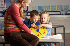 Female Teacher In Primary School Teaching Children. To Tell Time In Classroom stock photography