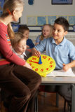 Female Teacher In Primary School Teaching Children Stock Photo