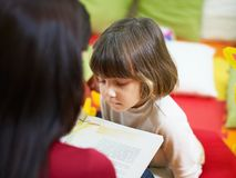 Female teacher reading book to little girl Stock Photo