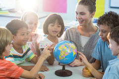 Female teacher showing globe to children. Smiling female teacher showing globe to schoolchildren in classroom stock photos