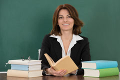 Female Teacher Sitting At Classroom Desk. Happy Young Female Teacher Sitting At Classroom Desk royalty free stock images