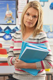 Female Teacher Sitting At Desk In Classroom Stock Photo