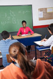 Female Teacher Sitting With Students In Classroom. Portrait of young female teacher sitting with students in classroom Royalty Free Stock Photography