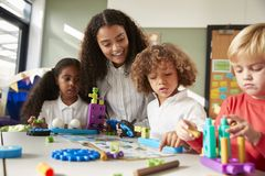 Female teacher sitting at table in play room with three kindergartne children constructing, selective focus stock photo
