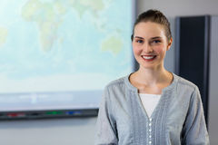 Female teacher standing against projector screen. Portrait of smiling female teacher standing against projector screen in classroom stock photos