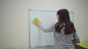 Teacher stands at whiteboard and explains rules of addition in elementary school. Female teacher stands at whiteboard and explains rules of addition in stock video footage