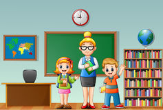 A female teacher with students in a classroom Royalty Free Stock Photos