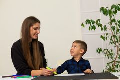 Female teacher teaches a little boy to draw at the table. Female teacher teaches a little boy to draw stock images