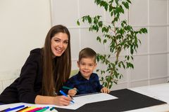 Female teacher teaches a little boy to draw at the table. Female teacher teaches a little boy to draw royalty free stock photo