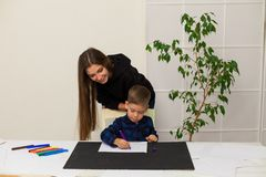 Female teacher teaches a little boy to draw at the table. Female teacher teaches a little boy to draw royalty free stock image