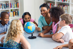 Female teacher teaching children using globe. Happy female teacher teaching children using globe on table in library royalty free stock photography