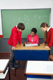 Female Teacher Teaching Teenage Students At Desk Royalty Free Stock Photos