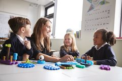 Female teacher and three primary school kids sitting at a table in a classroom working with educational construction toys, close u stock image