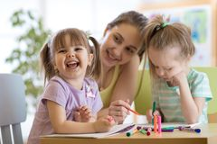 Female teacher working with kids in preschool classroom. Female teacher working with children in preschool classroom royalty free stock images
