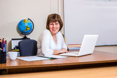 A female teacher works at a computer in the classroom Royalty Free Stock Photography