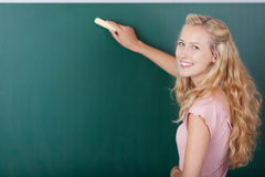 Female Teacher Writing On Chalkboard While Looking Over Shoulder. Portrait of happy female teacher writing on chalkboard while looking over shoulder stock photo