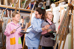 Female teachers assisting students. Glad female teachers assisting students during painting class at art studio stock images