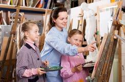 Female teachers assisting students. Happy female teachers assisting students during painting class at art studio Stock Image