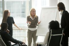 Female team leader or business coach giving presentation to empl. Female team leader or business coach gives presentation to multi-ethnic partners employees royalty free stock photos