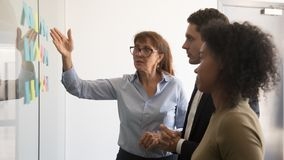 Female team leader explain project to colleagues with sticky notes. Middle aged female team leader talk explain project to multiracial team with sticky notes on royalty free stock image