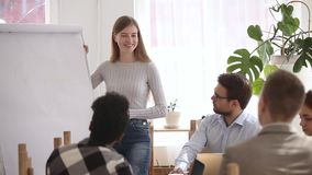 Female team leader showing quarter sales results use flip chart. Woman team leader reporting about quarter work shows diagram sales results use flip chart stock video footage