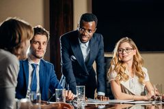 Female team leader talking with mixed race group of people in office. Female team leader talking with mixed race group of people on meeting in conference room Royalty Free Stock Photo