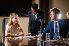 Female team leader talking with mixed race group of people in office. Female team leader talking with mixed race group of people on meeting in conference room Royalty Free Stock Images