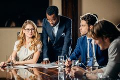 Female team leader talking with mixed race group of people in office. Female team leader talking with mixed race group of people on meeting in conference room Royalty Free Stock Photos