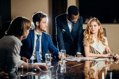 Female team leader talking with mixed race group of people in office. Female team leader talking with mixed race group of people on meeting in conference room Stock Photography