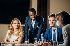Female team leader talking with mixed race group of people in office. Female team leader talking with mixed race group of people on meeting in conference room Royalty Free Stock Photography
