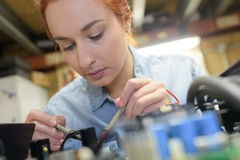 Female tech fixes electronic circuit Stock Images
