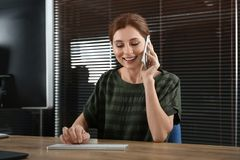 Female technical support operator talking on mobile phone stock image